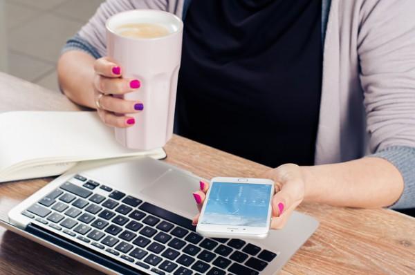 Жена с телефон и кафе в ръка